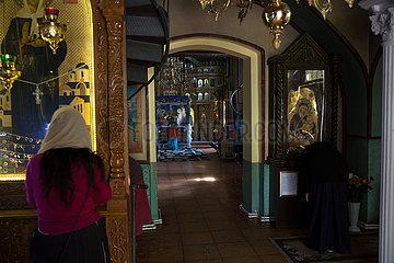 Republik Moldau  Glaeubige im Gebet vor Ikonen im Dreifaltigkeitskloster Saharna
