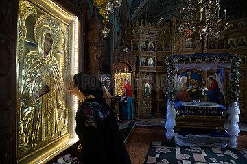 Republik Moldau  Nonne kuesst eine Ikone  hinten die Ikonostase  Dreifaltigkeitskloster Saharna