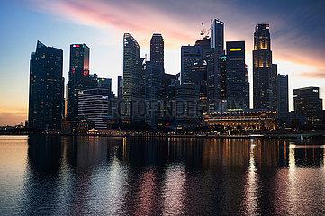Singapur  Republik Singapur  Blick ueber Marina Bay auf das Geschaeftsviertel mit Wolkenkratzern im Abendlicht