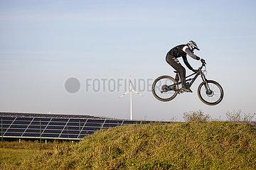 Mountainbikefahrer auf Mountainbike Arena vor Solarpark und Windrad  Dortmund  Ruhrgebiet  Nordrhein-Westfalen  Deutschland