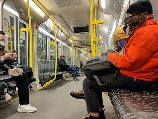 Fahrgaeste mit Maske in einer U-Bahn