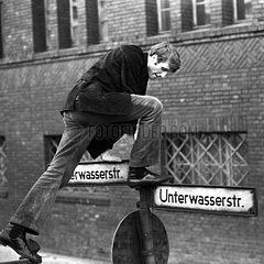 Berlin  Deutsche Demokratische Republik  Schauspieler Reiner Schoene klettert auf ein Strassennamenschild