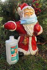 Berlin  Deutschland  Nikolausfigur traegt einen Mund-Nasen-Schutz  daneben eine Flasche mit Handdesinfektionsmittel
