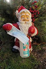 Berlin  Deutschland  Nikolausfigur haelt einen Mund-Nasen-Schutz in der Hand  darunter eine Flasche mit Handdesinfektionsmittel