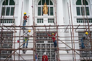 Singapur  Republik Singapur  Arbeiter bauen auf einer Baustelle ein hoelzernes Baugeruest ab