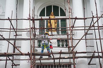 Singapur  Republik Singapur  Arbeiter mit Farbeimer steht auf dem hoelzernen Baugeruest einer Baustelle