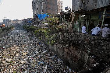 Mumbai  Indien  Ein mit Hausmuell und Plastikabfaellen uebersaehter Fluss in Mumbais Armenviertel Dharavi