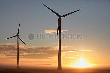 Neu Heinde  Deutschland  Windkraftanlagen bei Sonnenaufgang im Nebel