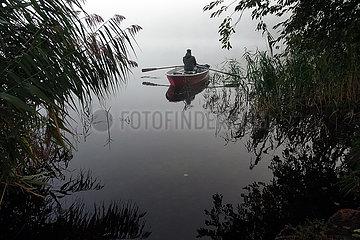 Dranse  Deutschland  Mann sitzt bei Nebel auf einem See in einem Ruderboot