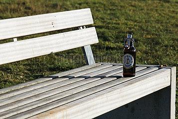 Berlin  Deutschland  Leere Bierflasche steht auf einer Parkbank