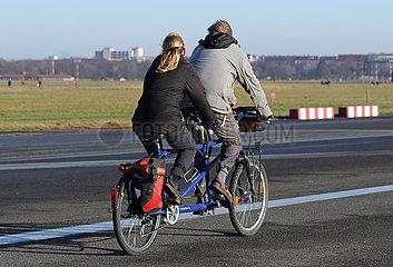 Berlin  Deutschland  Mann und Frau radeln auf einem Tandem ueber das Tempelhofer Feld