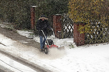 Berlin  Deutschland  Mann beseitigt vor seinem Grundstueck den frisch gefallenen Schnee vom Gehweg