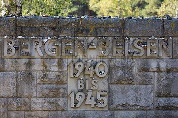 Deutschland  Lohheide - Gedenkstaette Bergen-Belsen  Schriftzug / Gedenktafel am Eingang zum frueheren Lagergelaende mit kleinen Steinen zum Gedenken  platziert von juedischen Besuchern