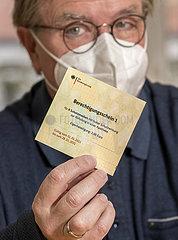 Risikopatient zeigt Berechtigungsschein  Gutschein fuer FFP2-Masken  Februar 2021