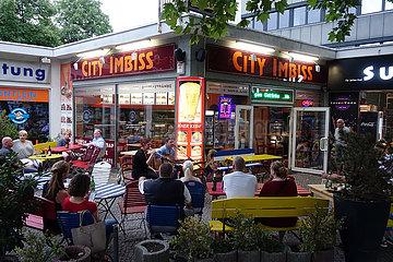 Berlin  Deutschland  Menschen vor einem Imbiss lauschen dem Gesang zweier Musiker
