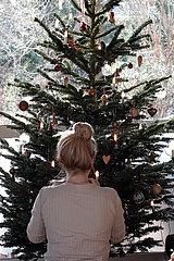 Berlin  Deutschland  Junge Frau schmueckt einen Weihnachtsbaum