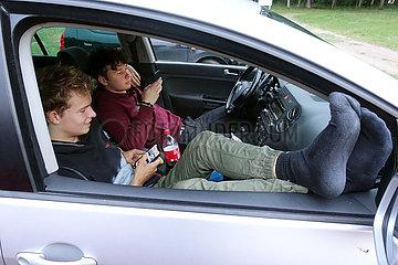Zempow  Deutschland  junge Maenner sitzen auf einem Parkplatz in einem Auto und schauen auf ihre Smartphones