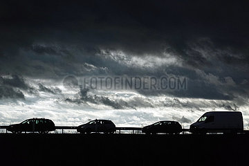 Berlin  Deutschland  Silhouette: Autos zeichnen sich auf einer Autobahnauffahrt gegen den dunklen Wolkenhimmel ab
