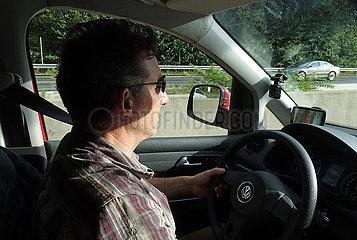 Bad Homburg  Deutschland  Mann mit Sonnenbrille faehrt in seinem Wagen entspannt auf der Autobahn