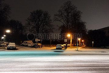 Berlin  Deutschland  Strasse ist in der Nacht leicht mit Schnee bedeckt