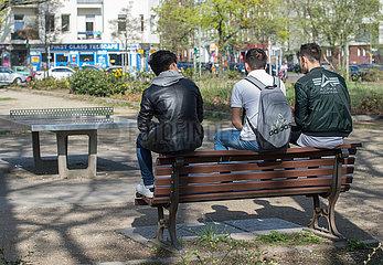Berlin  Deutschland - Jugendliche auf einer Bank am Leopoldplatz