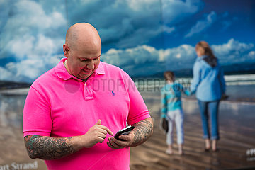 Grossbritannien  Nordirland  Belfast - Mann schreibt sms vor Werbeplakat