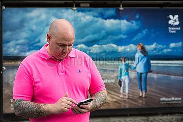 Grossbritannien  Nordirland  Belfast - Mann schreibt sms vor Werbeplakat des National Trust  gemeinnuetzige Organisation fuer Denkmalpflege und Naturschutz