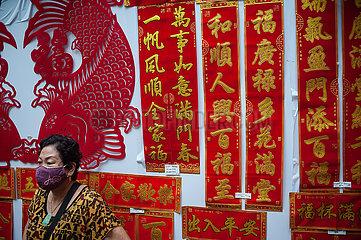 Singapur  Republik Singapur  Frau mit Mundschutz vor Spruchbaendern mit chinesischen Schriftzeichen in Chinatown