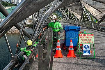 Singapur  Republik Singapur  Arbeiter mit Mundschutz reinigen die Helix-Bruecke in Marina Bay