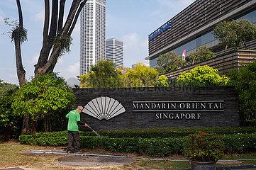Singapur  Republik Singapur  Arbeiter waessert am Mandarin Oriental Hotel in Marina Square die Pflanzen