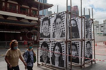 Singapur  Republik Singapur  Frauen mit Mundschutz gehen waehrend Corona-Pandemie an ausgestellten Portraits vorbei