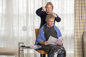 Frau schneidet ihrem Mann in Coronazeiten die Haare  Muenchen  Februar 2021