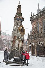 Deutschland  Bremen - Der Roland auf dem verschneiten Marktplatz in der Altstadt  davor ein italienischer Tourist