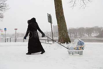 Deutschland  Bremen - Mutter zieht ihr Kleinkind in einem Waeschekorb uber den Schnee  hinten der Fluss Weser