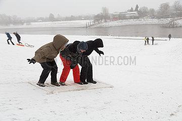 Deutschland  Bremen - Junge Leute surfen auf einem geliehenem Plastikteil einer Absperrung an der Weser im Schnee