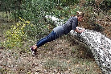 Walkmuehle  Deutschland  Frau macht im Wald an einem umgestuerzten Baum Liegestuetze