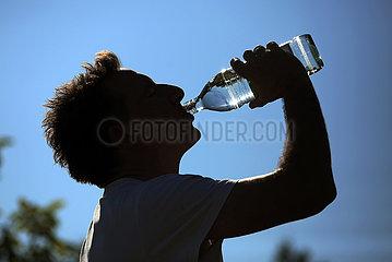 Ingelheim  Deutschland  Silhouette  Mann trinkt Wasser aus einer Glasflasche