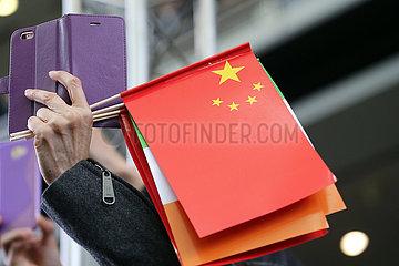 Hong Kong  China  Nationalfaehnchen der Volksrepublik China in der Hand eines Menschen