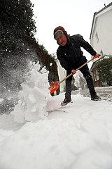Berlin  Deutschland  Mann schaufelt vor seinem Grundstueck den frisch gefallenen Schnee vom Gehweg
