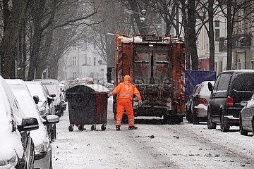Berlin  Deutschland  Mitarbeiter der BSR schieben bei Schneefall eine volle Restmuelltonne zur Entleerung an den Muellwagen
