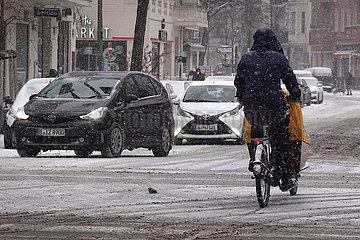 Berlin  Deutschland  Radfahrer faehrt bei Schneefall auf einer Strasse