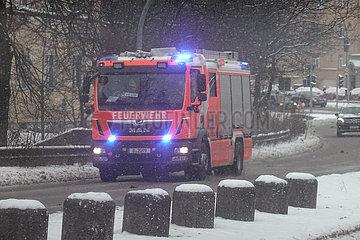Berlin  Deutschland  Loeschzug der Berliner Feuerwehr bei heftigem Schneefall auf Einsatzfahrt