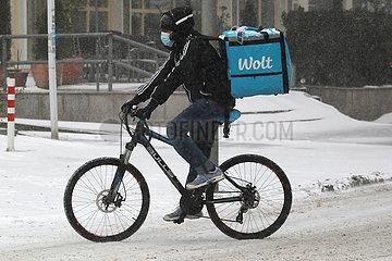 Berlin  Deutschland  Mitarbeiter des Wolt-Lieferservice faehrt bei Schneefall auf einem Fahrrad