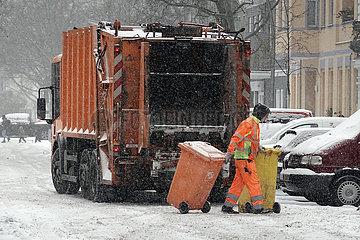 Berlin  Deutschland  Mitarbeiter der BSR zieht bei Schneefall geleerte Muelltonnen vom Muellwagen weg