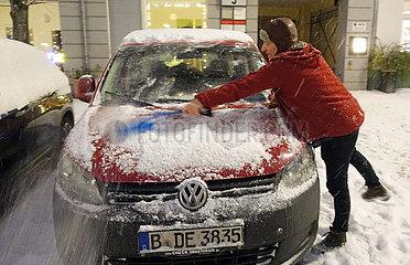 Berlin  Deutschland  Mann fegt am Abend den frisch gefallenen Schnee von seinem geparkten Auto