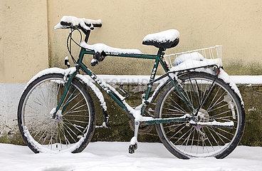 Graditz  Deutschland  Fahrrad lehnt mit Schnee bedeckt an einer Mauer