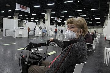 Seniorin mit Rollator wartet auf ihren Impftermin im Impfzentrum Köln
