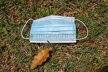 Singapur  Republik Singapur  Benutzter Mundschutz liegt auf dem Boden im Gras