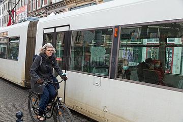 Deutschland  Bremen - Seniorin auf Fahrrad neben Strassenbahn