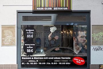 Deutschland  Bremen - Friseur putzt Fenster  Wiedereroeffnung nach der 2. Coronawelle